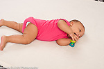 5 month old baby girl holding toy rolling over