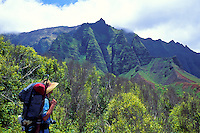 Hiker on the Kalalau Trail passes serrated cliffs