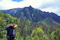 Hiker on the Kalalau Trail passes serrated cliffs