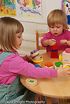 17 month old toddler girl playing w. blocks near sister age 4, playing with building toy