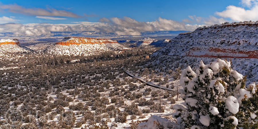 Near the old gate entrance to Los Alamos, New Mexico is the very scenic Clinton P Anderson Scenic Overlook.  A parking spot is often populated by several cars photographing and posing in front of the great view.