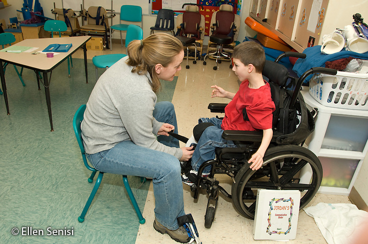 MR / Albany, NY.Langan School at Center for Disability Services .Ungraded private school which serves individuals with multiple disabilities.Teacher helps child put on his AFO's (Ankle foot orthotic). Boy: 9, cerebral palsy, limited verbal output with expressive and receptive language delays.MR: Ris4, Rub1.© Ellen B. Senisi