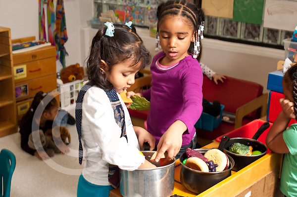 Education preschool 4 year olds pretend play two girls playing together in kitchen family area