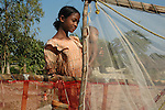 Swapna carrying her brother to work. She catches prawn seeds from the river and sell them in the local market. She earns about a dollar a day. Sunderban, West Bangal, India. Dec 2005. Arindam Mukherjee