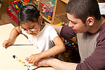 Education Preschool Headstart 3-4 year olds young male teacher working with girl counting sorting animal-shaped beads