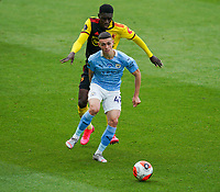 Phil Foden of Man City holds off Ismaila Sarr of Watford during the Premier League match between Watford and Manchester City at Vicarage Road, Watford, England on 21 July 2020. Football Stadiums around remain empty due to the Covid-19 Pandemic as Government social distancing laws prohibit supporters inside venues resulting in all fixtures being played behind closed doors until further notice.<br /> Photo by Andy Rowland.