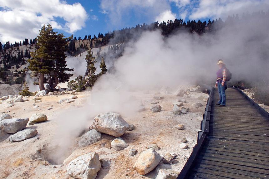 Steam engulfs Christine Kolisch on a wooden pathway at the  hot sulphur springs of BUMPASS HELL - LASSEN NATIONAL PARK -  CALIFORNIA