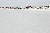 Tuesday March 13, 2012   A team on Golovin Bay with Golovin in the background.  Iditarod 2012.
