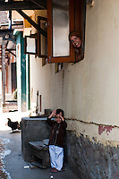 Smiling young boy waves to viewer as mother looks on from window, Srinagar, Kashmir, India.