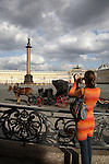 A visitor taking photos of Palace Square with Alexander Column and a horse carriage in the background. St. Petersburg. Russia