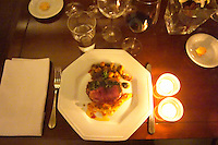 A slice of juicy red roast beef with green herb sauce and yellow tomato and vegetable coulis, roast potatoes served to the guest on the table with candles and wine glasses. The Dolly Irigoyen - famous chef and TV presenter - private restaurant, Buenos Aires Argentina, South America Espacio Dolli
