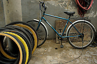 Bicycle and old bike tires are lined up in preparation at a repairman's stall, Hutong District, Beijing, China.
