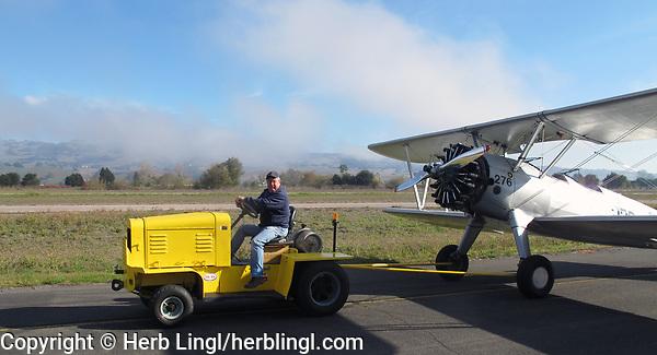 Pilot and aircraft mechanic Roger Willis tows his Stearman to an aircraft display exhibition at the Petaluma Municipal Airport, Petaluma, Sonoma County, California with his natural gas powered tractor.