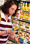 College student female shopping at supermarket, reading labels on butter and margarine packages