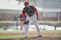 Batavia Muckdogs relief pitcher Nestor Bautista (39) looks in for the sign in the rain as the sun shines during a game against the West Virginia Black Bears on June 25, 2017 at Dwyer Stadium in Batavia, New York.  Batavia defeated West Virginia 4-1 in nine innings of a scheduled seven inning game.  (Mike Janes/Four Seam Images)