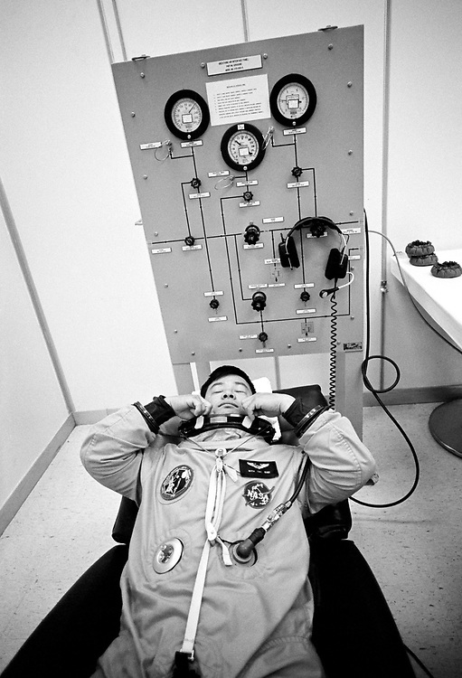 Image copyright John Angerson. <br /> STS-72 mission training.<br /> Mission Specialists Leroy Chiao is fitted into his spacesuit before flight simulation. Leroy Chiao went on to be the Commander of Expedition 10 on the International Space Station, 2005. <br /> Kennedy Space Centre, Florida, USA.