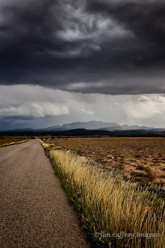 An old paved road fading into the distance with grass along the edge and a stormy sky above.