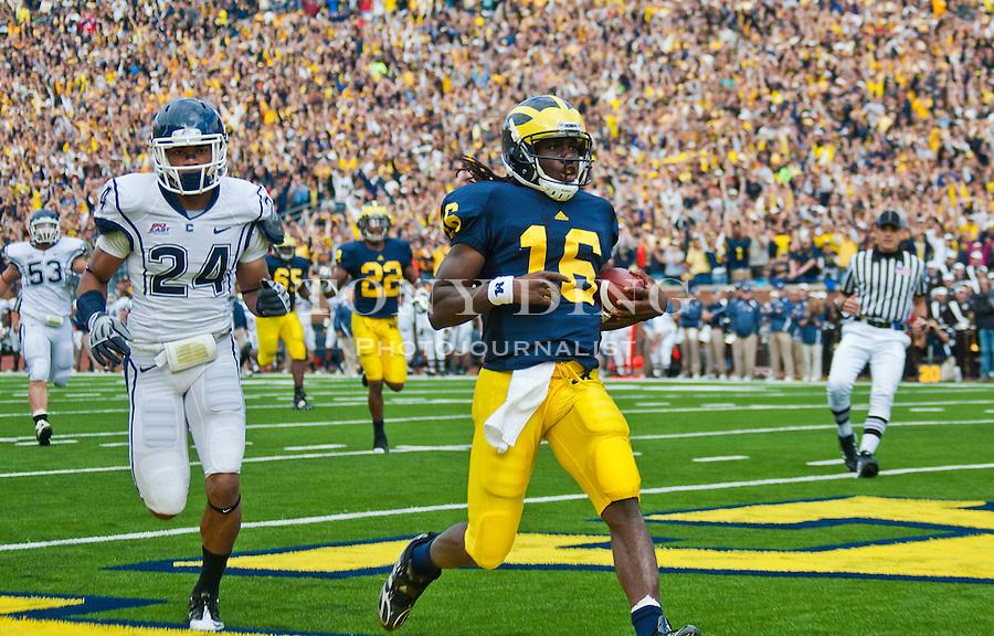 Michigan quarterback Denard Robinson (16) scores a touchdown, followed by Connecticut cornerback Dwayne Gratz (24), in the first quarter of an NCAA college football game, Saturday, Sept. 4, 2010, in Ann Arbor, Mich. (AP Photo/Tony Ding)