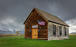 Gallatin County, Montana: Old Sedan Church (1898) with flag flying and storm clouds