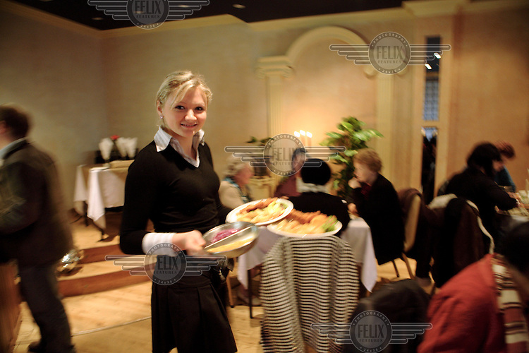 First generation Polish waitress working at the dining room in the White Eagle Polish Club in Balham, London. The Polish community regularly come here on Sundays for lunch after church, and Saturday nights host traditional Zabawa dance classes.