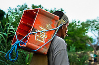 A contraband smuggler carries an empty box on the shore of the river Tachira on the Colombia-Venezuela border, 2 May 2006. Venezuelan gasoline, being 20 times cheaper than in Colombia, is the most wanted smuggling item, followed by food and car parts, while reputable Colombian clothing flow to Venezuela. There are about 25,000 barrels of gasoline crossing illegally the Venezuelan border every day. The risky contraband smuggling, especially during the rainy season when the river rises, makes a living to hundreds of poor families in communities on both sides of the frontier.