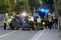 Pictured: Emergency services attend the scene of a car accident where a Hyundai car landed on its roof in Swansea, Wales, UK. Wednesday 28 July 2021<br /> Re: Police, fire service personnel and paramedics have attended an incident in which a Hyundai landed on its roof on Oystermouth Road by the Tesco supermarket in Swansea, Wales, UK.