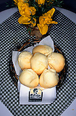 Brazil. Basket of Pao de Queijo, traditional cheese bread, on a checked tablecloth.
