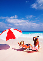 Couple relaxing at the beach with chairs and umbrella
