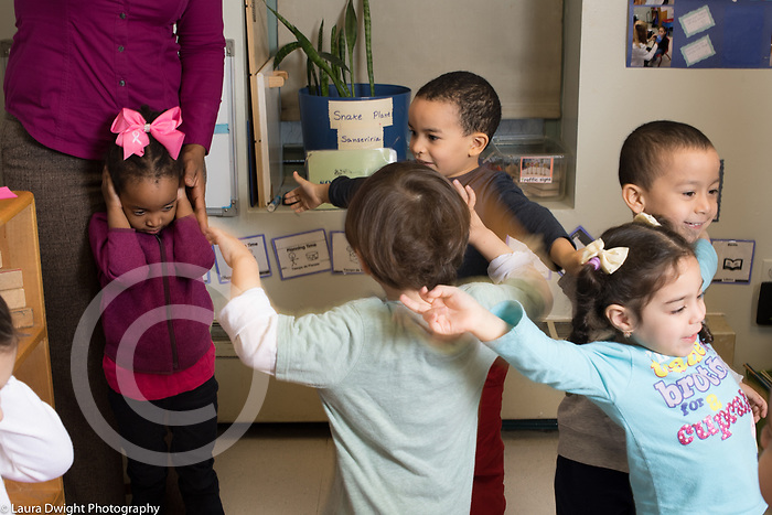 Education Preschool 3-4 year olds girl covering her ears to block sound as classmates sing and move to song