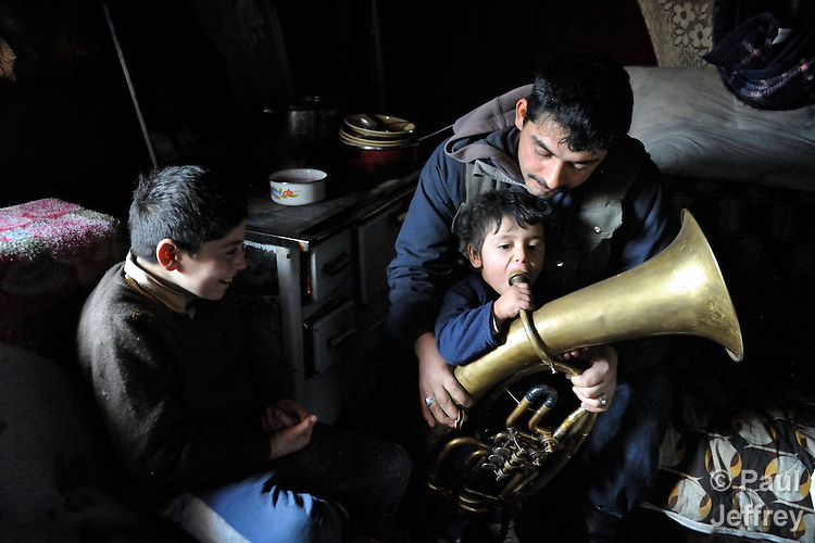 "THIS PHOTO IS AVAILABLE AS A PRINT OR FOR PERSONAL USE. CLICK ON ""ADD TO CART"" TO SEE PRICING OPTIONS.   Milan Pesic gets help from one of his children as he practices his french horn inside his home in a Roma settlement in Belgrade, Serbia. He plays in a Roma band. The families that live here, many of whom survive from recycling cardboard and other materials, are under constant threat of eviction in order to make way for new high-rise office buildings."