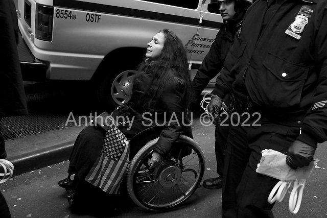 """New York, New York<br /> November 17, 2011<br /> <br /> """"Occupy Wall Street"""" protesters mark the movement's two-month milestone by marching from Zuccotti Park, in mass, to various access streets surrounding the New York Stock Exchange, which the police had barricaded off. Yet instead of the police keeping protesters out, protesters locked down those entrances to Wall Street and the New York Stock Exchange creating havoc as the police made more then 240 arrests to try and keep the streets open to normal traffic.<br /> <br /> At Williams and Pine street, NYPD arrest dozens of protesters,  including this woman in a wheelchair. The anti-Wall Street protesters intention to disrupting business as usual on Wall Street was successful."""