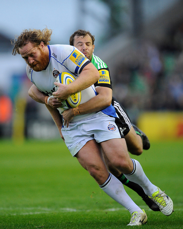 Ross Batty of Bath Rugby is tackled by Nick Evans of Harlequins