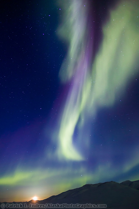 Aurora borealis streak heavenward over the Chandalar Shelf, Brooks Range, Arctic Alaska, moon rises in the distance on the vernal equinox, march 21st, 2003 at 1:00 a.m.