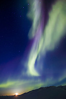 Aurora borealis streak heavenward over the Chandalar Shelf, Brooks Range, Arctic Alaska, moon rises in the distance on the vernal equinox, march 21st, 2003 at 1:00 a.m.