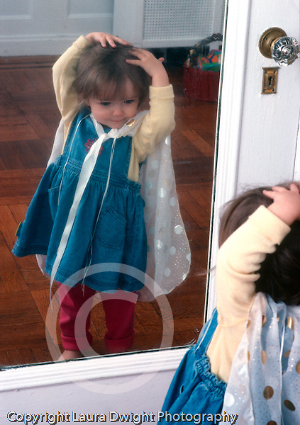Toddler girl 18 months old looking at self in mirroring hands on head wearing dressup cape recognizing self vertical Caucasian