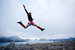 A man wearing a red wig and maple leaf shorts jumps off a rock in Canada's Arctic near Qikiqtarjuaq in the territory of Nunavut.