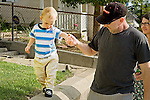 Father with cap on head holds toddler son's hand as child walks on ledge of wall as Mom looks concerned