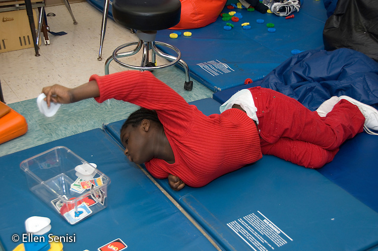 MR / Albany, NY.Langan School at Center for Disability Services .Ungraded private school which serves individuals with multiple disabilities.Girl lies on mat and practices grasping and manipulating objects as she plays with cards. Student is wearing a diaper. Like some people with cerebral palsy, her muscles are not capable of allowing her to manage her toileting independently. Girl: 10, African-American, cerebral palsy, expressive and receptive language delays.MR: And6.© Ellen B. Senisi