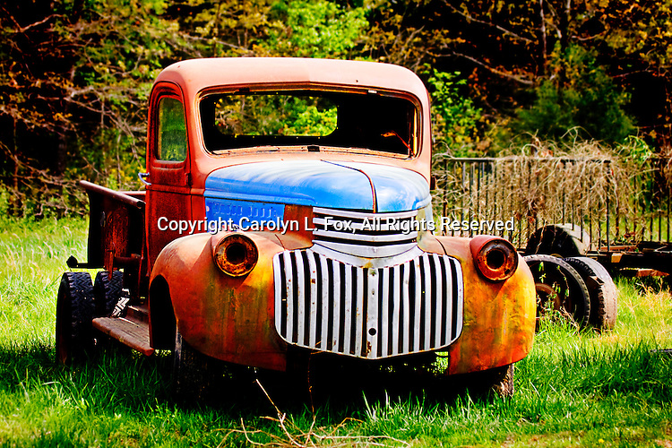 A rusty old truck sits in a field in the mid-section of the USA.
