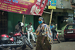 A sex worker pases by wearing a mask at Sonagachi in Kolkata. Sonagachi is the biggest red light area in Asia. Sex workers are not getting any customers during the lock down and are in bad economic condition. Police, NGOs and local authoritis are providing them with food.  India is going through a 21 days lock down due to covid 19 pandemic. Kolkata, West Bengal, India. Arindam Mukherjee.