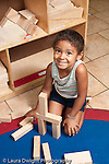 Education Preschool 3-5 year olds block area girl building with wooden blocks proud smiling posing for camera vertical
