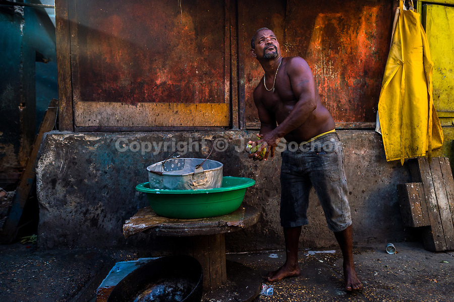 An Afro-Colombian man washes cooking pots at the end of the shift in a street restaurant in the market of Bazurto in Cartagena, Colombia, 5 December 2018. Far from the touristy places in the walled city, a colorful, vibrant labyrinth of Cartagena's biggest open-air market sprawls to the Caribbean seashore. Here, in the dark and narrow alleys, full of scrappy stalls selling fruit, vegetables and herbs, meat and raw fish, with smelly garbage on the floor and loud reggaeton music in the air, the African roots of Colombia are manifested.