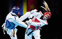10 AUG 2012 - LONDON, GBR - Carmen Marton (AUS) (right) of Australia tries to evade a kick from Sousan Hajipourgoli of Iran during their women's -67kg category preliminary round contest at the London 2012 Olympic Games Taekwondo at Excel in London, Great Britain (PHOTO (C) 2012 NIGEL FARROW)