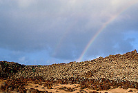 Hawaiian Mookini heiau, a religious place of worship, found in Kohala with a rainbow in the background