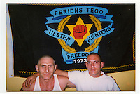 A photograph from Graeme's family album: Graeme (left) beneath an Ulster Freedom Fighters (UFF) pennant in 2003. These flags were banned as part of the Good Friday Agreement since they are a sign of open support for a terrorist organisation.
