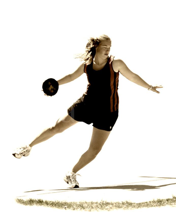 Teenage girl throwing discus in track meet