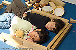 Education preschool 3-4 year olds horizontal pretend play boy and girl pretending to nap inside block structure they built