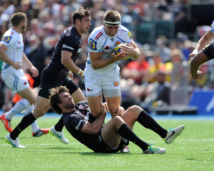Marcelo Bosch of Saracens hangs onto the legs of Sam Hill of Exeter Chiefs