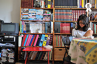 Teenager girl reading in living room by bookcase (Licence this image exclusively with Getty: http://www.gettyimages.com/detail/92351853 )