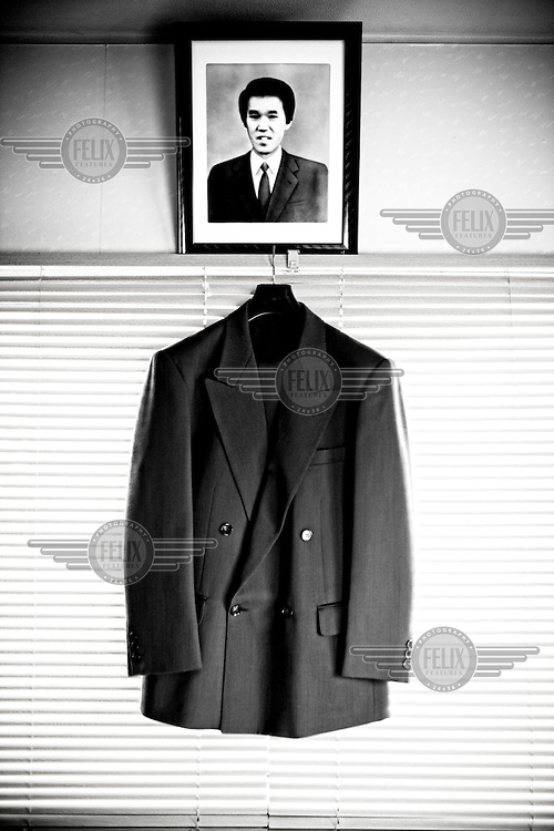 """A jacket that belonged to Akira Teranishi is seen with his photo in Kyoto. Akira was a restaurant manager and worked 12-14 hours a day for more than 10 years. His excessive overwork and stress brought depression on him eventually and he ended his life by jumping from a building on a snowy Valentine's Day. """"Pain never goes away no matter how much time passes. After my husband's death, children grew up, got married, and grandchildren were born. More things to celebrate in my life, more sadness I feel, because I always wished my husband was here with me to share joy."""" says his wife Emiko.."""